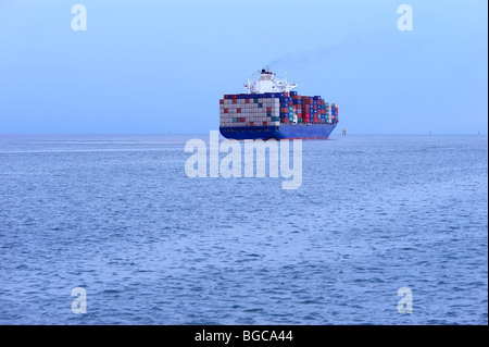 Container ship heading out to sea - Stock Image
