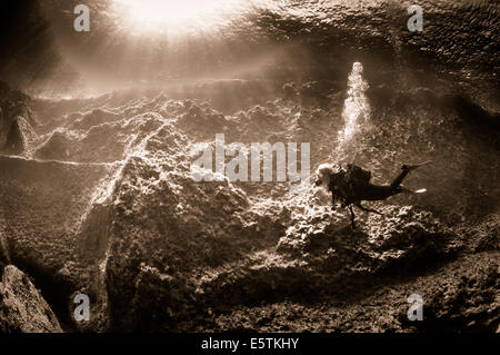 Monochrome view of a young female scuba diver swimming along a limestone reef with shafts of sunlight streaming - Stock Image