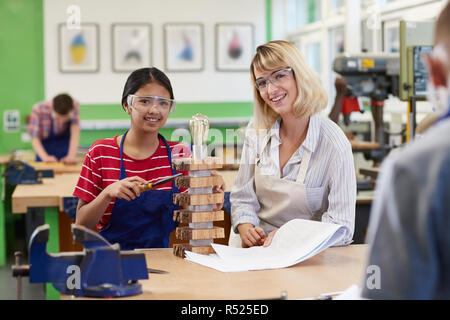 Portrait Of Teacher Helping Female High School Student Building Lamp In Woodwork Lesson - Stock Image