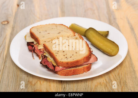 Pastrami sandwich on Jewish Rye bread with swiss cheese, mustard, and kosher dill pickles - Stock Image