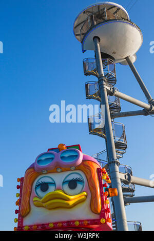 Fairground ride with zipwire launch tower towering behind on Bournemouth Pier at Bournemouth, Dorset UK in July - Stock Image