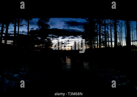 Okefenokee swamp with remnant of sunset after dark; boat light in distance. Deep blue sky, silhouette of forest, fading orange light. - Stock Image
