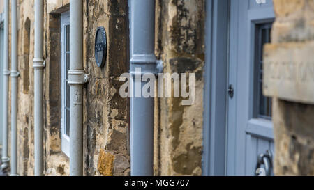 Cast iron water downpipes line up agaist the limestone walls of  terraced cottages in the Cotswold's market town of Chipping Campden - Stock Image