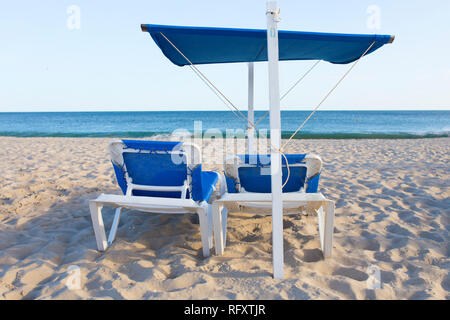 Beach chair with awning structure for sunshade. Beach background - Stock Image