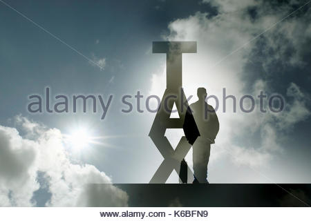 Transparent businessman and the word 'tax' back lit by sunny sky - Stock Image