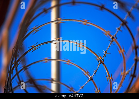 RAZOR WIRE, BARBED WIRE, DANGER, CAUTION, KEEP OUT, FENCE, METAL, SAFETY, WIRE, SKY, BOUNDAR - Stock Image
