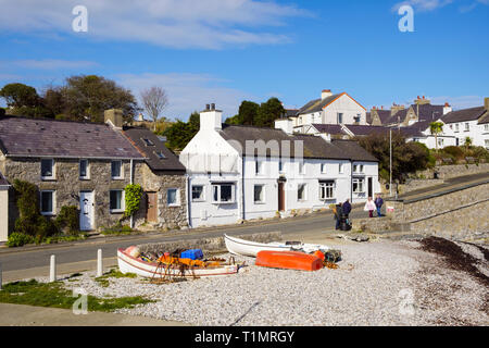 View to cottages on waterfront with fishing boats on beach in village of Moelfre, Isle of Anglesey, Wales, UK, Britain - Stock Image