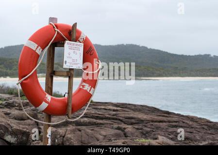 A life bouy or floatation device mounted near a popular rock fishing area at Kioloa Beach on the New South Wales south coast of Australia - Stock Image