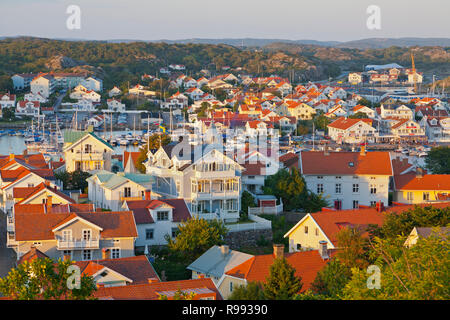 Evening view at sunset of historical and car-free island Marstrand in the west coast archipelago, Sweden. Painted wooden houses with red tile roofs. - Stock Image