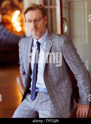 Man wearing glasses looking apprehensive - Stock Image