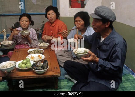 Northern China 1980 Commune in Waoning Province in an interior of a home where a family are eating a meal sitting on a kang a bed stove which is a platform made of brick where funnelled air is fuelled by a fire providing heat, usually wood fire. - Stock Image
