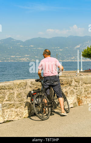 TORRI DEL BENACO, LAKE GARDA, ITALY - SEPTEMBER 2018: Person on a bicycle stopped on the promenade in Torri del Benaco on Lake Garda to look at the la - Stock Image