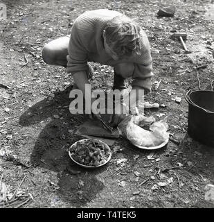 1960s, historical, adventure scout in the forest at an outdoor activity course perparing food - strips of meat for a stew?, England, UK. - Stock Image