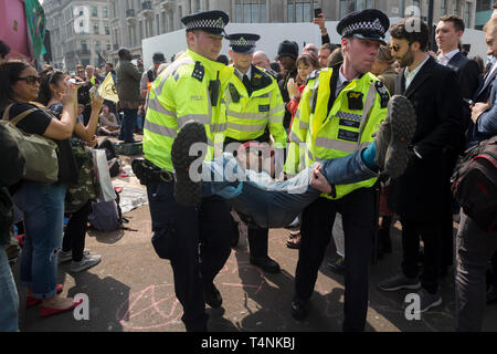 An activist with Extinction Rebellion is arrested during the London protest about climate change in a blocked-off Oxford Circus , on 17th April 2019, in London, England. - Stock Image