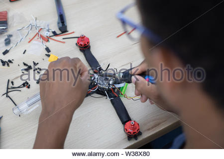 Black man mounting and soldering racing drone on wooden table - Stock Image