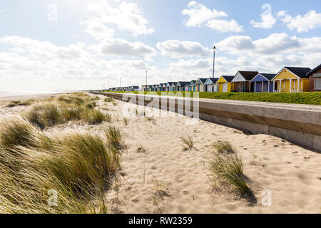 Sutton On Sea, Lincolnshire, UK. 04th Mar, 2019. UK Weather: 04/03/19 Bright, sunny but very windy day sand dunes of Sutton On Sea, Lincolnshire, East coast, UK England. Clouds forming over the Chalets lining the sea front. beach chalet, beach chalets, sutton on sea chalets, colourful Credit: Tommy  (Louth)/Alamy Live News - Stock Image