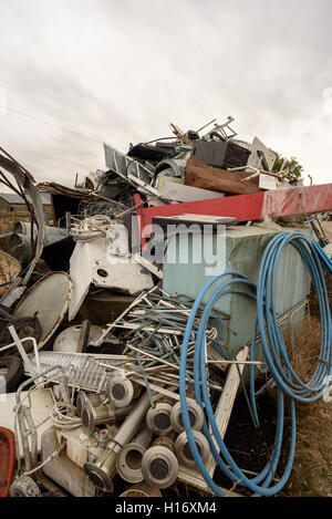 Assorted stack of scrap metal and household appliances for recycling at a merchants - Stock Image