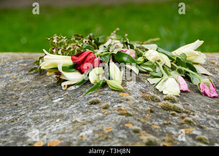 Wilted flowers resting on a grave in an English churchyard - Stock Image