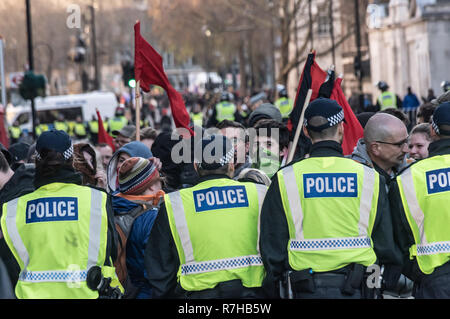 London, UK. 9th Dec, 2018. Police stop anti-fascists as they try to leave Whitehall to disperse at Charing Cross station. They had taken part in the united counter demonstration by anti-fascists in opposition to Tommy Robinson's fascist pro-Brexit march. Police had issued conditions on both events designed to keep the two groups well apart. Credit: Peter Marshall/Alamy Live News - Stock Image