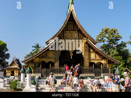 Western tourists removing shoes to enter 16th century sim at Wat Xieng Thong temple. Luang Prabang, Louangphabang province, Laos, southeast Asia - Stock Image