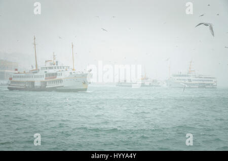 Ferry boats sail along the Golden Horn on a foggy winter's day in Istanbul - Stock Image