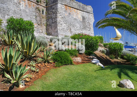 Palm trees and the wall of an ancient fortress. Resort town Cascais. A suburb of Lisbon, Portugal. - Stock Image