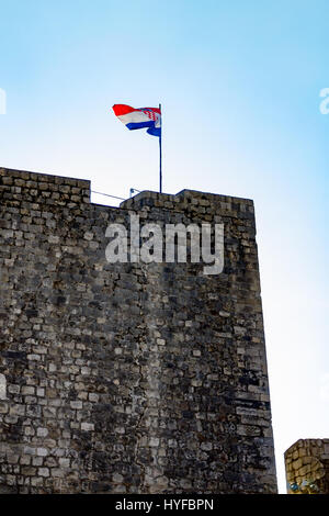 The Croatian flag flys over the old walled city in Dubrovnik - Stock Image