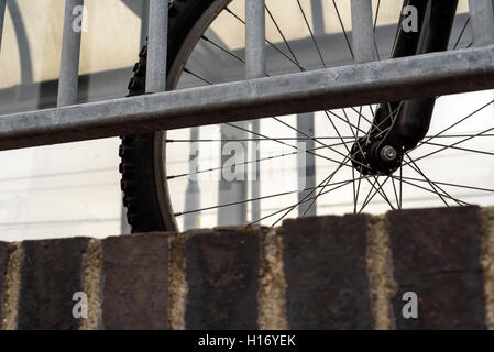 Parked commuter bike with a railing. Single cycle tyre and spokes are visible through the railings - Stock Image