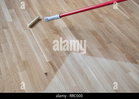 lacquering Varnishing a polished oak parquet floor by paint roller first layer. - Stock Image