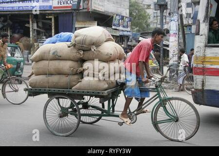 BANGLADESH Many carrying heavy load on bicycle cart. Dhaka photo by Sean Sprague - Stock Image