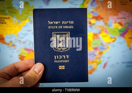 Hand holding the passport of the State of Israel against the colorful world map atlas. Israel citizenship concept, Israeli biometric 'darkon' passport - Stock Image