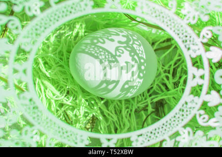 Easter. A beautiful Easter card with an openwork oval frame through which beautiful shadows fall on a white egg. Green background, top view. - Stock Image