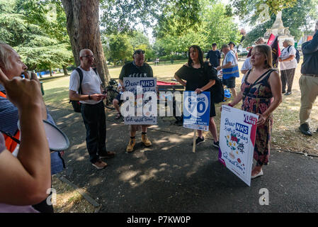 London, UK. 7th July 2018. Keep Our St Helier Hospital (KOSHH) campaigners against the closure of acute facilities at Epsom and St Helier Hospitals in south London meet in a Sutton park to celebrate the 70th Birthday of the NHS with a march from Sutton to a rally in front of St Helier Hospital.  The closures are prompted by government cuts which call for huge savings by the trust, and would l Credit: Peter Marshall/Alamy Live News - Stock Image