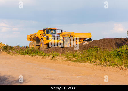 A pair of Volvo articulated A30G dumper trucks parked facing in opposite directions in golden setting sun at Cumberwell landfill - Stock Image