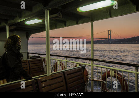 A woman watches the Bosphorus bridge from a ferry boat, at sunset. - Stock Image
