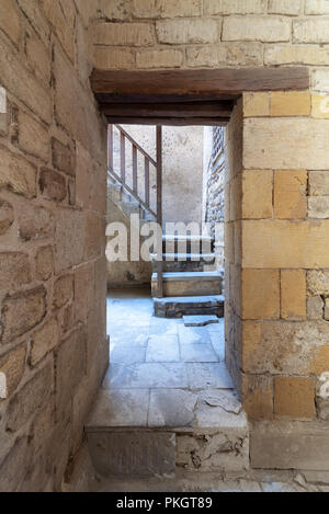 Ancient external old bricks stone wall and doorway revealing a stone staircase with wooden balustrade, Old Cairo, Egypt - Stock Image