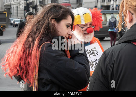 London, UK. 11th January 2019. A man in a clown headress has the message on his back '16 years of Guantanamo Is no laughing matter' at the protest  by the Guantanamo Justice Campaign and London Guantanamo Campaign marking the 17th anniversary of the first prisoners arriving at the illegal US camp. A display of posters, photographs of the remaining detainees, readings and speeches in Trafalgar Square highlighted the abuse, torture, lack of human rights, force-feeding and indefinite detention there. Credit: Peter Marshall/Alamy Live News - Stock Image