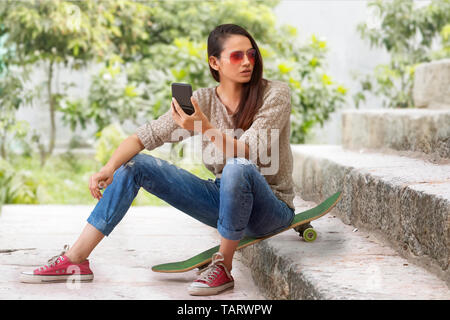Woman sitting on skateboard on steps holding a small mirror - Stock Image
