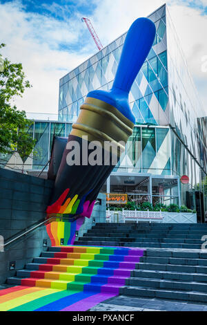 Giant inflatable paintbrush with rainbow colours, celebrating Pride festival.  At The Avenue, Spinningfields, Manchester, England, UK - Stock Image