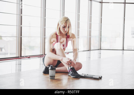 Relaxing after training. View of beautiful young woman looking away while sitting on exercise mat at gym - Stock Image