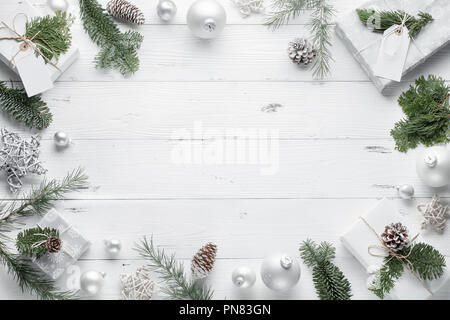 Christmas gift, knitted blanket,Christmas balls and fir branches on wooden white background. Flat lay,top view. - Stock Image