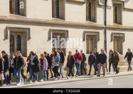 A party of schoolchildren walk up the High Street, Oxford past Magdalen College - Stock Image