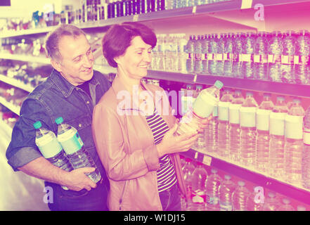 Happy couple with a bottle of water at the grocery store - Stock Image