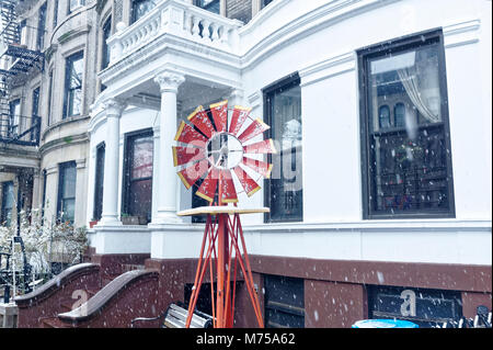 Small red decorative windmill in an urban neighborhood during a light snowfall. - Stock Image