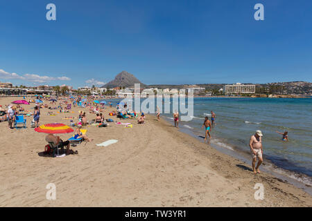Javea Spain Playa del Arenal beach with people walking by the sea and swimming - Stock Image
