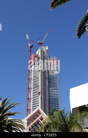 CONSTRUCTION OF A HIGH RISE RESIDENTIAL TOWER WITH CRANES AGAINST A BRIGHT BLUE SKY VERTICAL BDB - Stock Image