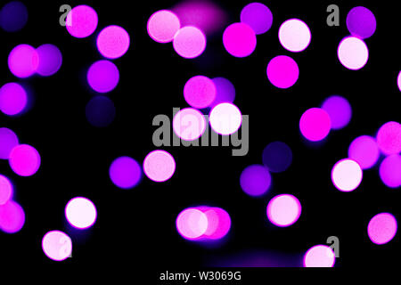 Unfocused abstract purple bokeh on black background. defocused and blurred many round light. - Stock Image