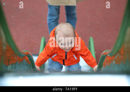 Baby Boy With Orange Raincoat Climbing Up The Slide, Close Up Portrait View - Stock Image