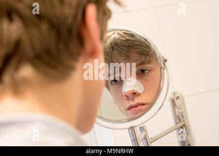 Fair-haired teenage boy looks in a bathroom mirror at his spots wearing a blackhead strip on his nose as part of a skincare routine - Stock Image