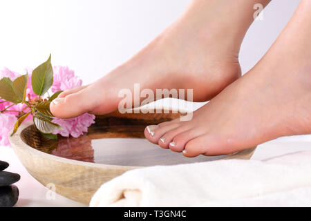 Beautiful female feet in spa studio with french nails polish. Girl legs on wooden bowl with water and pink flowers and towel isolated on white - Stock Image